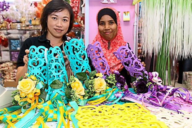Ideal as decorations: Wong (left) and her staff holding up the decorative pieces they have created using colourful foam sheets, artificial flowers and ribbon ketupat.
